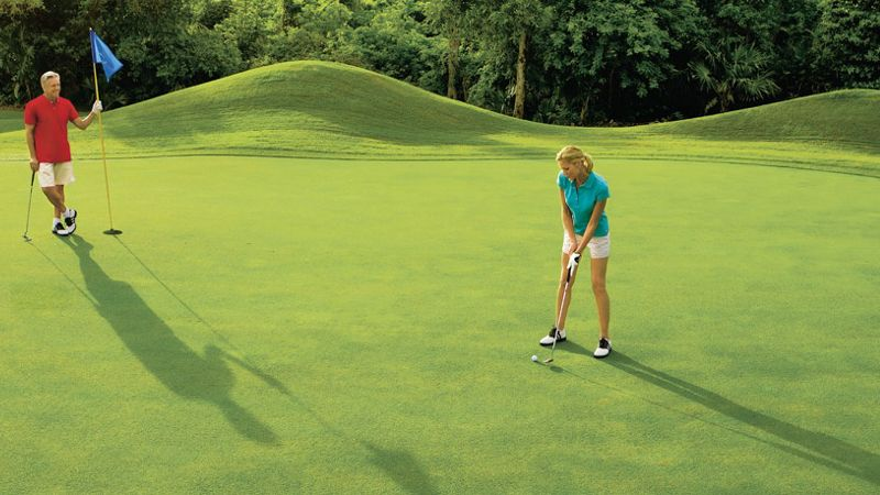 adult couple playing golf