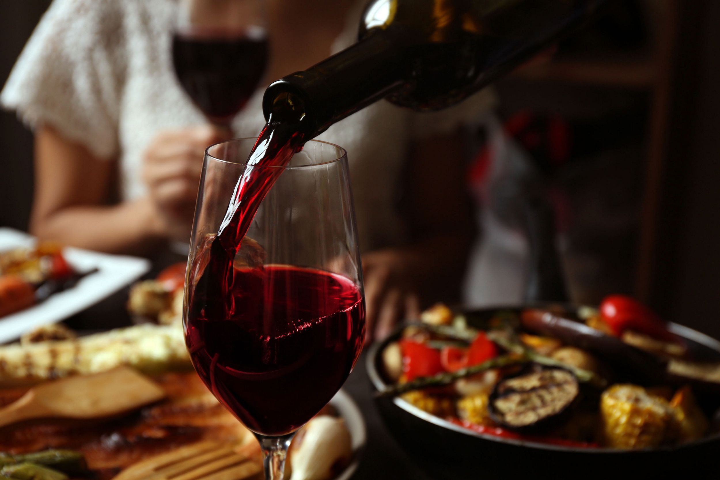 Red wine being poured into a glass with food in the background