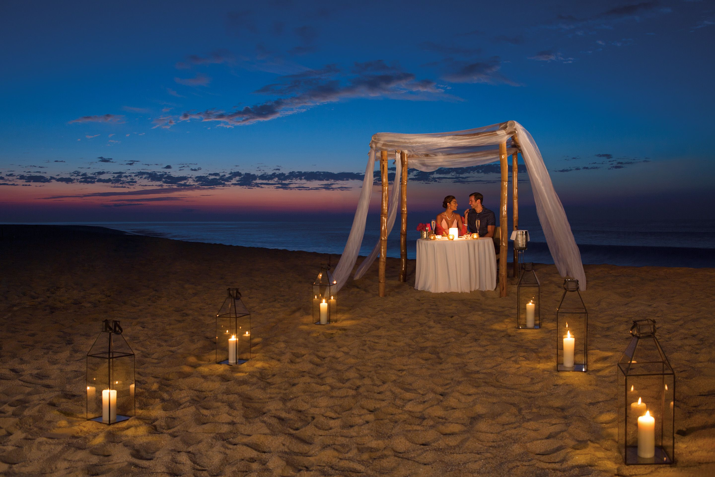 Romantic dinner setup on the beach at night