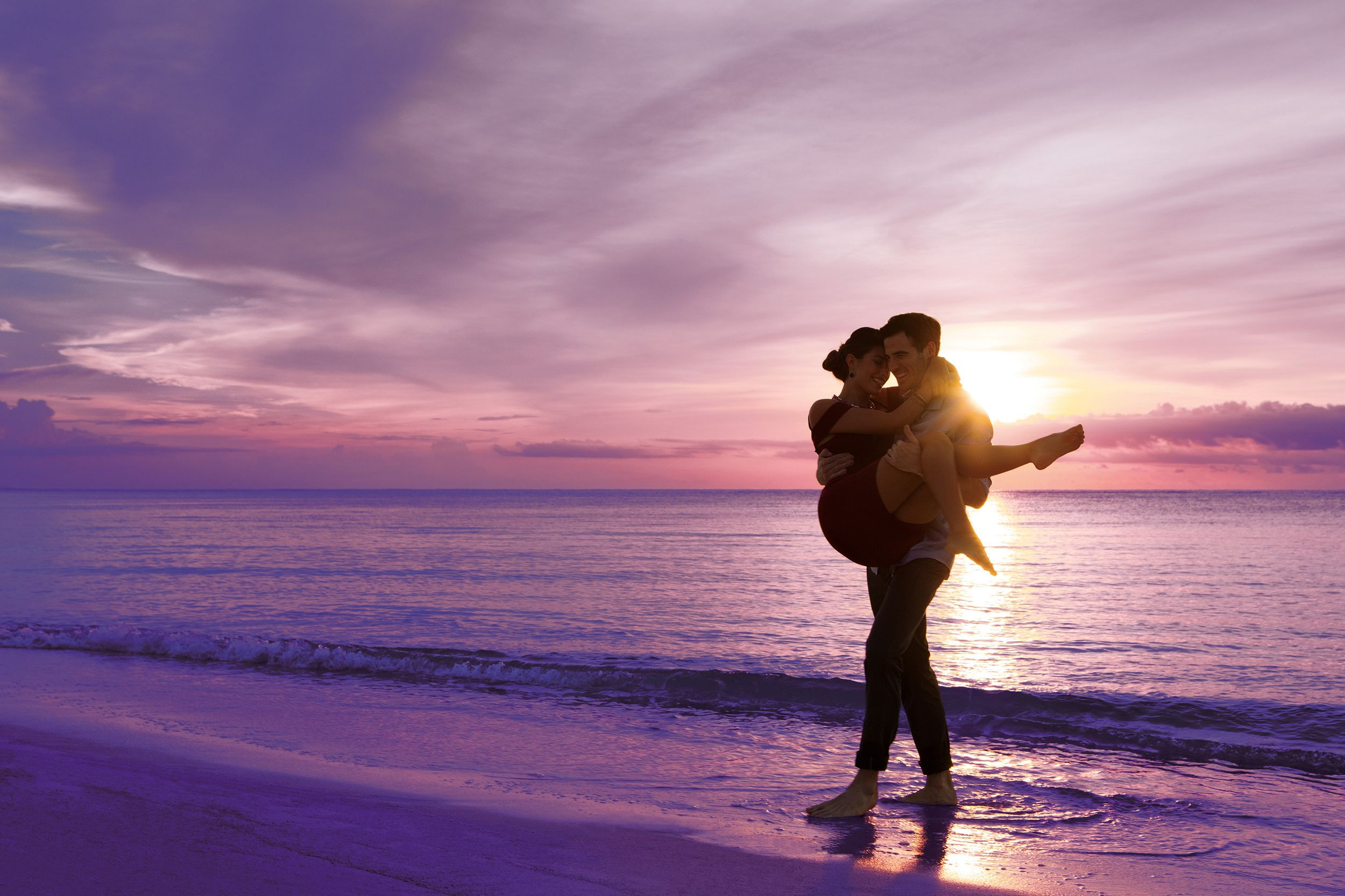 couple by the ocean at sunset