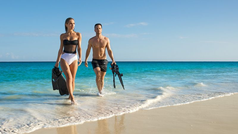 couple on the beach holding snorkeling gear