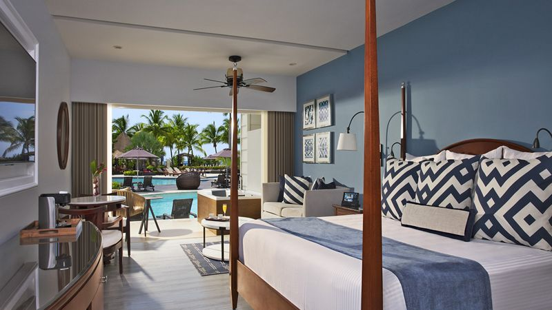 King bed blue bedroom with couch and tv and swim out to pool, ocean in the background